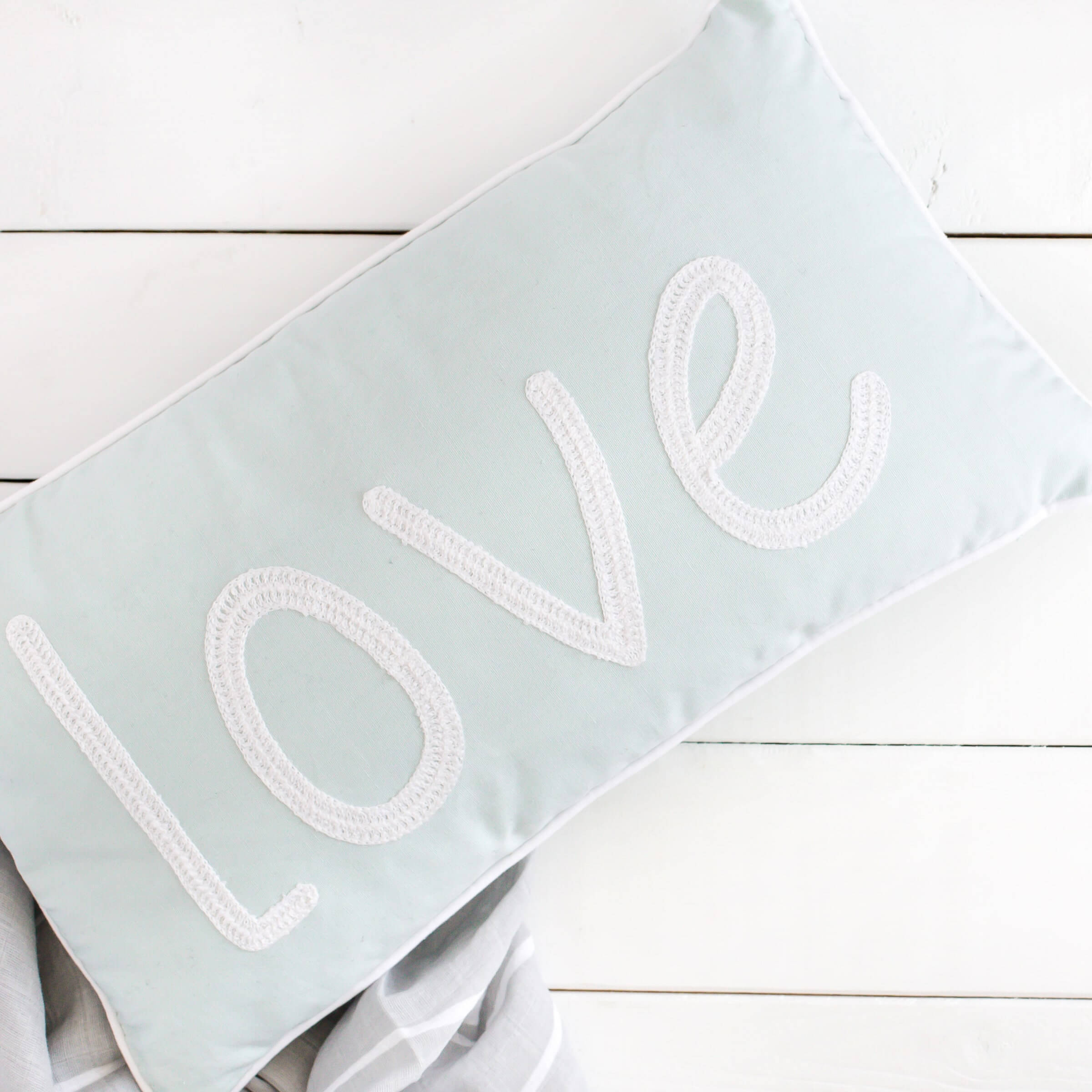 Cushion with embroidered love lettering
